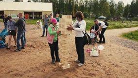 Jeu de jenga de jeu de fille grand avec l'homme adulte sur le sable Festival de famille d'été Gosses clips vidéos