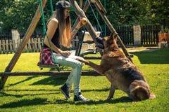 Jeu de jeune femme avec son chien en été Image stock