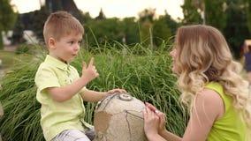 Jeu de mère et de fils en parc par temps chaud d'été avec la statue d'une tortue clips vidéos