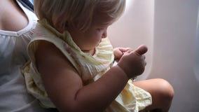 Jeu de petit enfant avec la boucle de ceinture de sécurité dans l'avion banque de vidéos