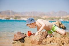 Jeu de petit garçon avec le sable sur la plage d'été Images libres de droits