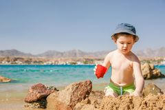 Jeu de petit garçon avec le sable sur la plage d'été Photographie stock