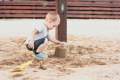 Jeu de petit garçon avec le sable sur la plage d'été photo stock