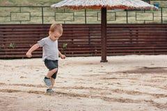 Jeu de petit garçon avec le sable sur la plage d'été images stock
