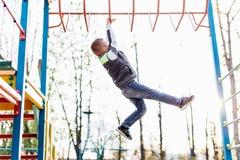Jeu de petit garçon sur le terrain de jeu avec le fond de parc de tache floue Photo stock