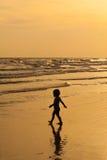 Jeu de petite fille à la fin de mer de coucher du soleil  Photos stock