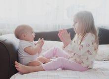Jeu de petite soeur avec ses mains Photographie stock libre de droits