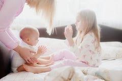 Jeu de petite soeur sur des mains dans le lit Image libre de droits