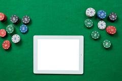 Jeu de poker en ligne avec le comprimé numérique et les piles de puces Images stock