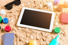 Jeu de poker en ligne sur la plage avec le comprimé numérique et les piles de puces Vue supérieure Photos libres de droits