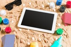 Jeu de poker en ligne sur la plage avec le comprimé numérique et les piles de puces Vue supérieure Images libres de droits