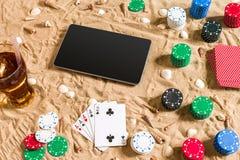 Jeu de poker en ligne sur la plage avec le comprimé numérique et les piles de puces Vue supérieure Photographie stock libre de droits