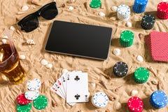 Jeu de poker en ligne sur la plage avec le comprimé numérique et les piles de puces Vue supérieure Images stock