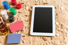 Jeu de poker en ligne sur la plage avec le comprimé numérique et les piles de puces Vue supérieure Photo stock