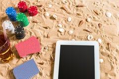 Jeu de poker en ligne sur la plage avec le comprimé numérique et les piles de puces Vue supérieure Photographie stock