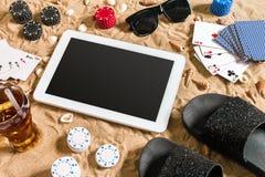 Jeu de poker en ligne sur la plage avec le comprimé numérique et les piles de puces Vue supérieure Image libre de droits