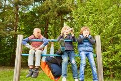 Jeu de quatre enfants sur un cadre de s'élever images libres de droits