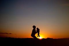 jeu de silhouettes de père et d'enfant au coucher du soleil Famille heureux Photos libres de droits
