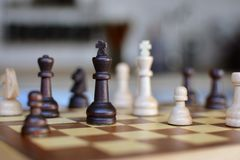 Jeu de société d'échecs avec le foyer sur les morceaux noirs et blancs de reine sur le fond trouble photographie stock libre de droits