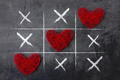 Jeu de Tac Toe de tic le jour du ` s de Valentine sur un fond foncé Images stock