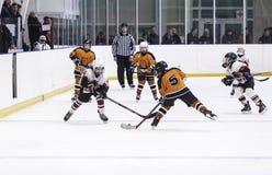 Jeu entre les équipes de glace-hockey d'enfants Image libre de droits