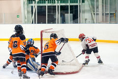 Jeu entre les équipes de glace-hockey d'enfants Photos stock