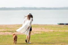 Jeu et fonctionnement asiatiques de femme de mode de vie avec le chien d'amiti? de golden retriever dans le lever de soleil ext?r photo stock