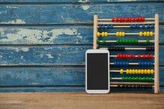 Jeu et smartphone d'Abbacus sur le fond en bois Images stock