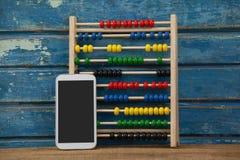 Jeu et smartphone d'Abbacus sur le fond en bois Photo stock