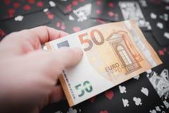 jeu 50 euros dans une main au-dessus de jouer noir carde le fond Photo stock