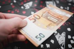 jeu 50 euros dans une main au-dessus de jouer noir carde le fond Photos stock