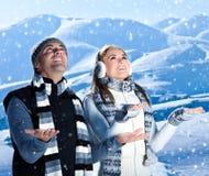Jeu heureux de couples extérieur aux montagnes de l'hiver Photographie stock libre de droits