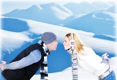 Jeu heureux de couples extérieur aux montagnes de l'hiver Photo stock