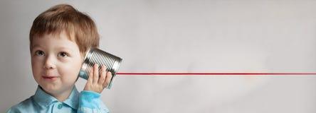 Jeu heureux de garçon dans le téléphone de boîte en fer blanc photographie stock