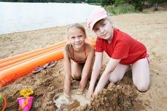 Jeu heureux de petites filles sur la plage de sable image libre de droits