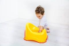 Jeu infantile d'enfant en bas âge de bébé garçon d'enfant avec le pot de selles de toilette de pot sur un fond blanc Photo stock