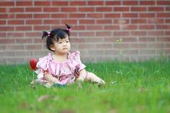 Jeu innocent mignon de bébé sur la pelouse Image stock