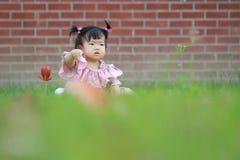 Jeu innocent mignon de bébé sur la pelouse Images stock