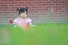 Jeu innocent mignon de bébé sur la pelouse Photos libres de droits