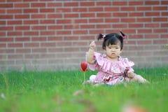 Jeu innocent mignon de bébé sur la pelouse Photographie stock