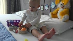 Jeu mignon de garçon avec des jouets de cuisine se reposant sur le lit L'enfant heureux ont l'amusement à la maison banque de vidéos