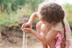 Jeu mignon de petite fille avec le sable en parc un jour d'été au sunse Photos libres de droits