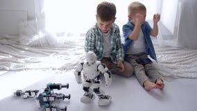 Jeu robotique de technologie, petits garçons examinant des robots avec les téléphones portables ensemble à la maison au week-end