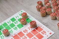 Jeu se développant de loto de jeu de table de bingo-test vieux avec les éléments en bois et bingo-test de cartes sur un fond en b Images libres de droits