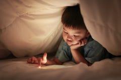 Jeu sur Internet d'Internet de jeu d'enfant, sous la couette photographie stock libre de droits