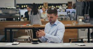 Jeugdige aantrekkelijke jonge zakenman die acties met zijn tabletpc uitvoeren, bij de lunchtijd in koffie stock videobeelden