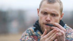 Jeugdige bruin-gebaarde mens met het expressieve gezicht spelen op lippen muzikaal instrument op het plattelandslandschap, Steun stock videobeelden