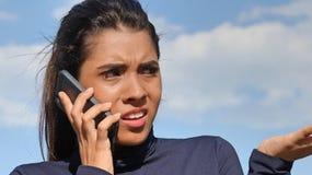 Jeugdige Columbiaanse Vrouwelijke Gebruikende Celtelefoon en Ongelukkig Stock Afbeelding