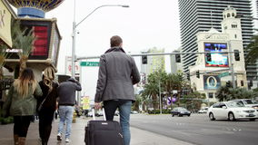 Jeugdige knap met een bagage en een kop van koffie loopt onderaan een stoep in Las Vegas stock video