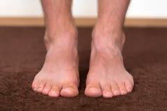 Jeukerige koude voeten die op de vloer rusten Royalty-vrije Stock Afbeeldingen